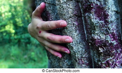 Horror Scene with Bloody Hand hiding behind tree