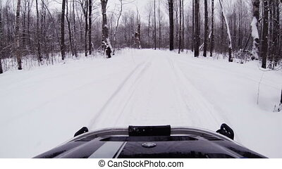 Snowmobile rides in the winter woods.