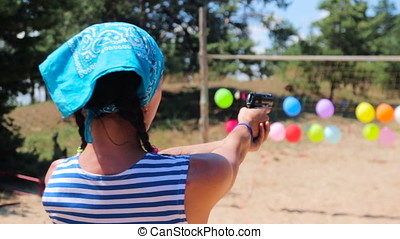 Girl shoot at balloons from gun at volleyball field