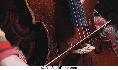 kid playing of old shabby cello