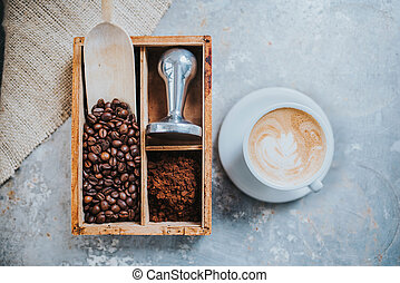 Cup of delicious coffee - Coffee beans, tamper and a cup of...