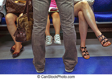 Riders on a Subway - Peoples legs on a subway