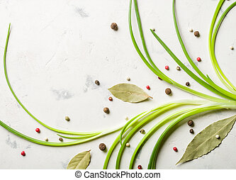 Spring onions with spices and bay leaf on a light stone...