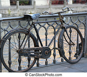 black old bike leaning on the bridge above the river - black...