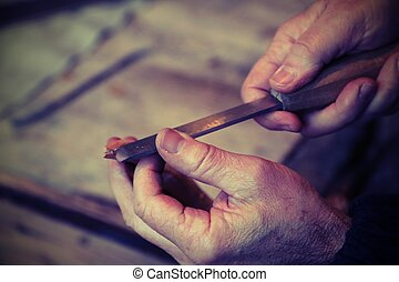 hands of an elderly carpenter while the piece of wood with a...