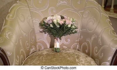 Bridal bouquet on chair in room