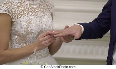 Bride puts on ring to groom's hand on ceremony - Bride puts...