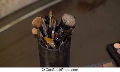Makeup palettes and brushes on table