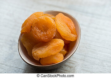 dried apricots in brown plate on a white background. Close-up