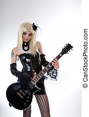 Sexy gothic girl with guitar, studio shot over white...