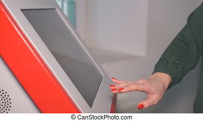 Monitor Touchscreen ATM - A woman uses an ATM to withdraw...