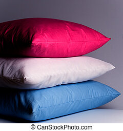 pink, white and blue pillows close up