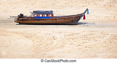 Long tail boat on sand beach