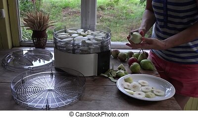 girl hands peeling and slicing pears on table near food dryer machine.