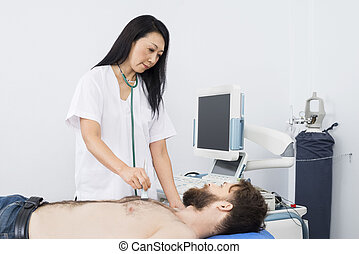 Doctor Examining Patient With Ultrasound Machine - Mature...