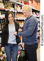 Customers Using Smart Watch In Grocery Store - Mature male...