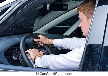 Driving man - Young man driving a car in a relaxed position