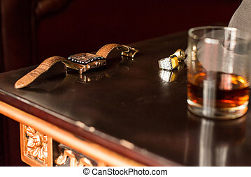 Men's watch and ring on the wooden retro table