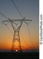 Electricity pylons at sunset - High tension electricity...