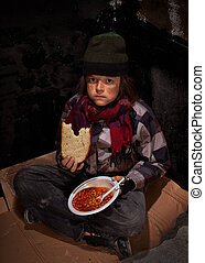 Worried young homeless boy eating charity food