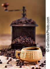 A cup of coffee and old coffee grinder