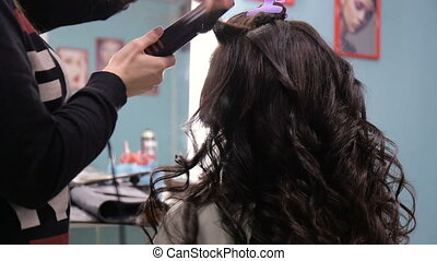 Stylist makes laying girl with long hair in a beauty salon. Full hd video