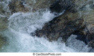 River Rushing Over Colorful Rocks - Closeup of river flowing...