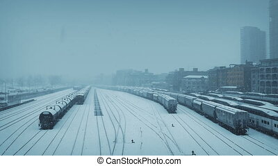 City Train Yard In Blizzard - Train yard by city buildings...