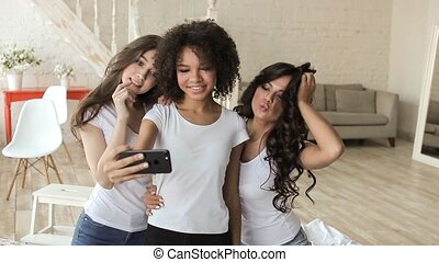Beautyful girls in white t-shirt make selfie sitting on bed.