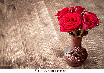 Roses in a vase on wooden background
