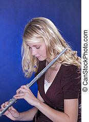 Flute Player Isolated on Blue - A blond teenage female girl...