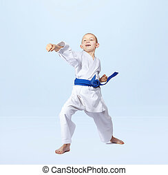 With a blue belt karateka strikes straight punch arm