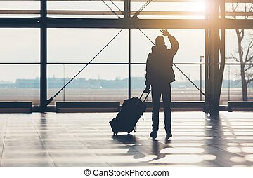 Saying goodbye at the airport. Silhouette of the traveler...