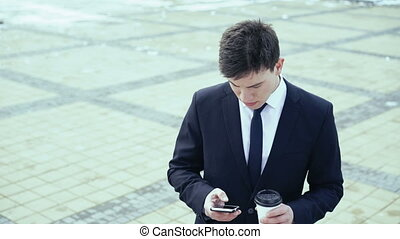 Young businessman drinking coffee outdoors and writing sms...