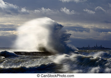 Wave splash at the pier on a stormy day Stormy weather at...
