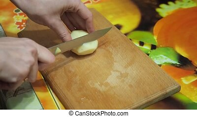 Young woman in the kitchen cutting the potatoes with knife on wooden cutting board