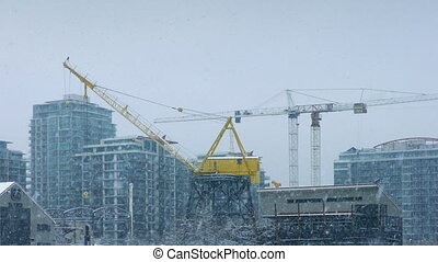 Large Cranes In City With Snow Falling - Cranes and...