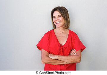 older woman smiling against gray wall with arms crossed -...