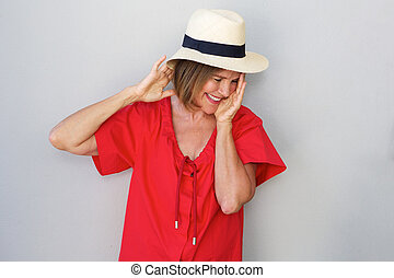 older woman laughing with hat against gray wall - Portrait...