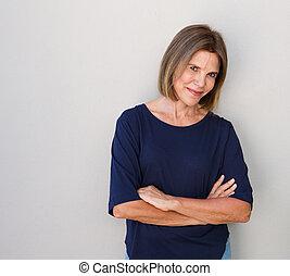 senior woman smiling against gray wall - Portrait of senior...