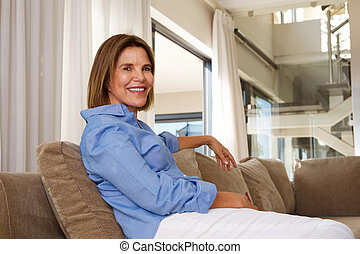 older woman sitting at home on sofa