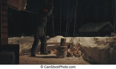 Young man chopping wood in the yard. Winter evening. Wide...