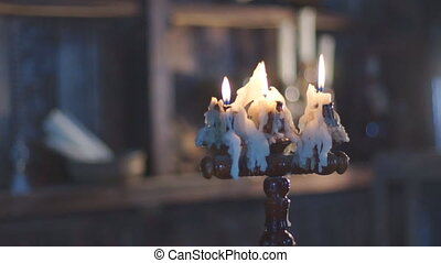 Three wax candles burning in candlestick