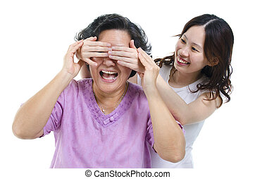 Daughter covering mother eyes - Portrait of Asian adult...
