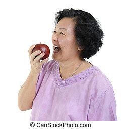 Senior adult woman eating apple