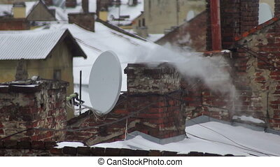 Smoke winter roof house - Smoke comes from the chimney of...