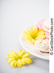 Macarons and yellow flowers - Close-up view of delicious...
