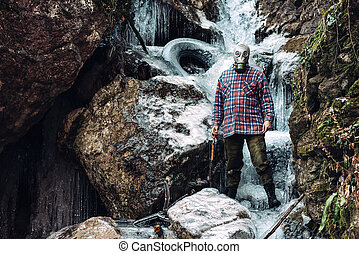 Scary man in the frozen waterfall