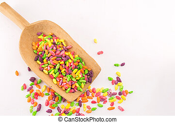 Colorful bonbons mix in wooden spoon