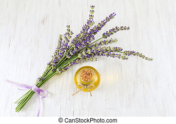 Lavender oil with fresh flower branches on a wooden table